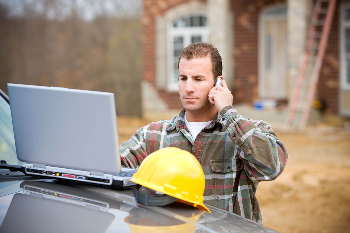 A contractor checking their email while calling a client about an assigned repair from TheQwikFix